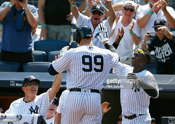 Aaron Judge of the New York Yankees is greeted by manager Joe Girardi and Didi Gregorius after he hit a home run in his first MLB at bat during the...