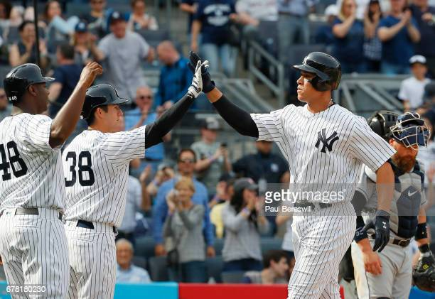 Aaron Judge of the New York Yankees is greeted by teammates Chris Carter and Kyle Higashioka after hitting a home run during the 7th inning of an MLB...