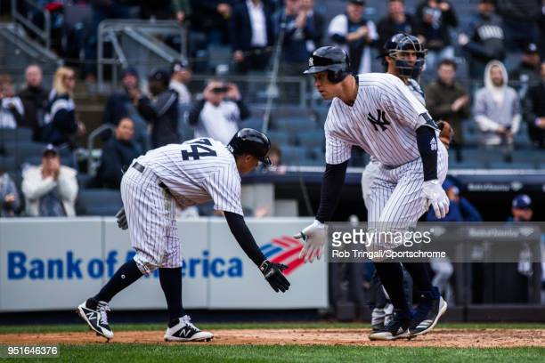 Aaron Judge of the New York Yankees low fives Ronald Torreyes after hitting a home run during the game against the Tampa Bay Rays at Yankee Stadium...