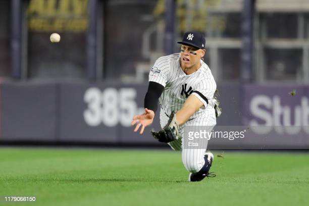 Aaron Judge of the New York Yankees makes a diving catch hit by Jorge Polanco of the Minnesota Twins during the third inning in game one of the...
