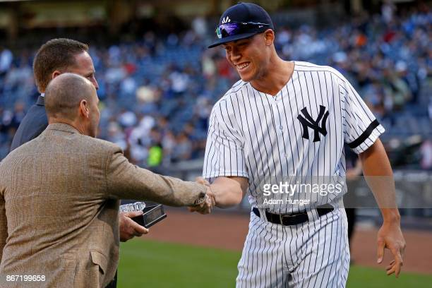 Aaron Judge of the New York Yankees shakes hands with Brian Cashman general manager of the New York Yankees prior to a game against the Toronto Blue...