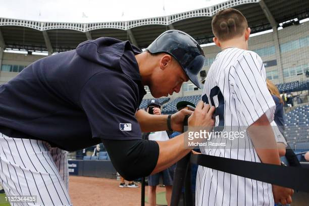 Aaron Judge of the New York Yankees signs a autograph for a fan prior to the Grapefruit League spring training game against the Philadelphia Phillies...