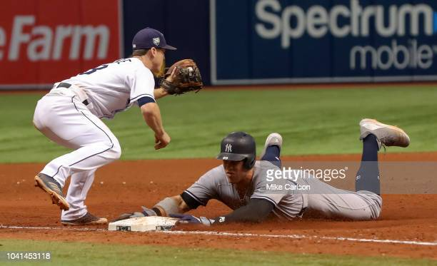 Aaron Judge of the New York Yankees slides in safely to third base ahead of a tag from Joey Wendle of the Tampa Bay Rays in the eighth inning of a...