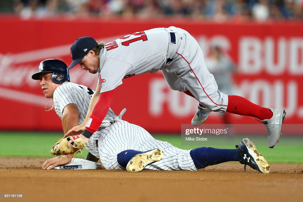 Aaron Judge #99 of the New York Yankees steals second base as Brock Holt #12 of the Boston Red Sox gets tripped up at Yankee Stadium on August 13, 2017 in the Bronx borough of New York City.