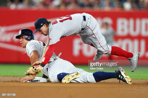 Aaron Judge of the New York Yankees steals second base as Brock Holt of the Boston Red Sox gets tripped up at Yankee Stadium on August 13 2017 in the...