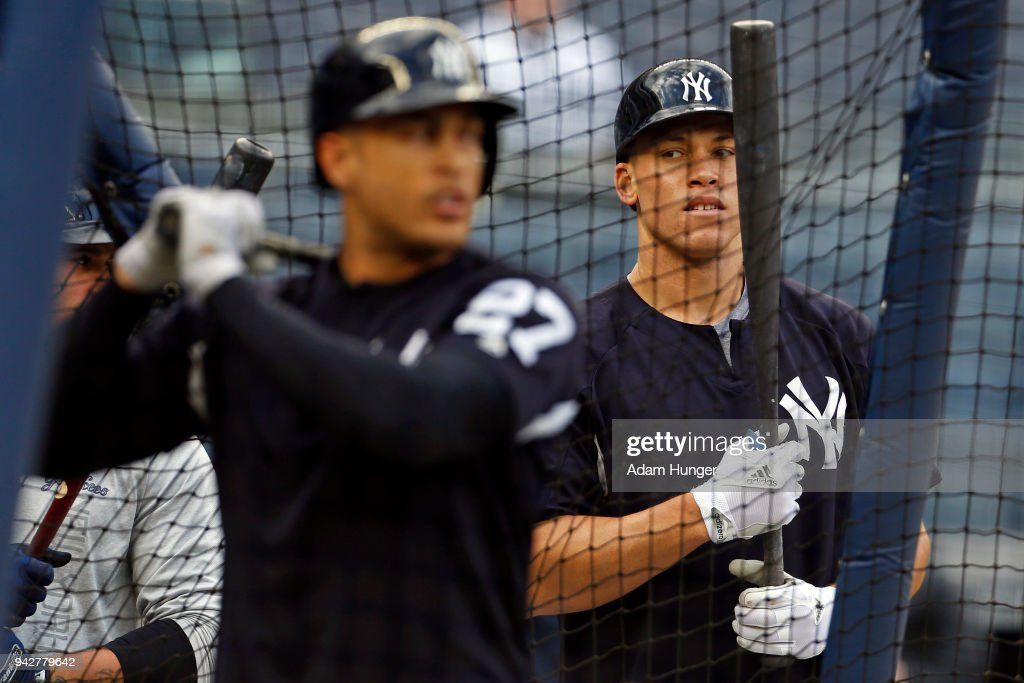 Aaron Judge #99 of the New York Yankees watches Giancarlo Stanton #27 of the New York Yankees during batting practice prior to their game against the Baltimore Orioles at Yankee Stadium on April 6, 2018 in the Bronx borough of New York City.