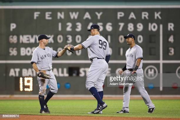 Aaron Judge Ronald Torreyes and Aaron Hicks of the New York Yankees high five each other after the victory over the Boston Red Sox at Fenway Park on...