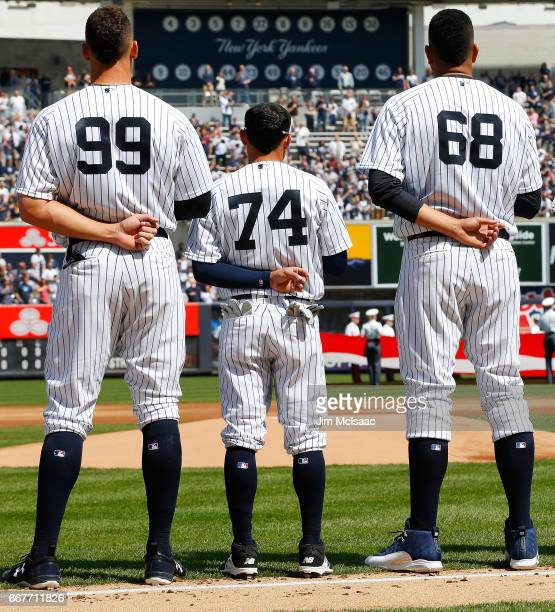 Aaron Judge Ronald Torreyes and Dellin Betances of the New York Yankees stand during the national anthem before their Opening Day game against the...