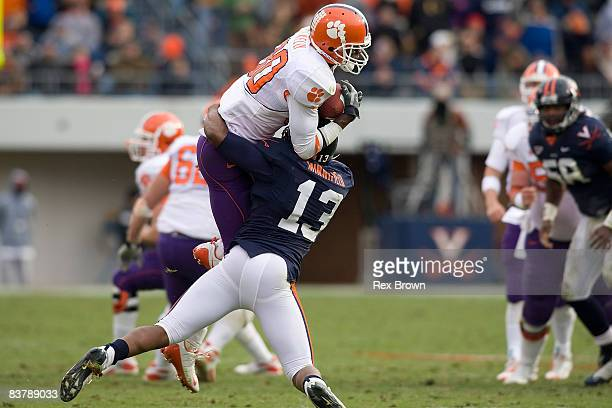 Aaron Kelly of the Clemson Tigers picks up this first down on a 4th down pass as Chase Minnifield of the Virginia Cavaliers applies the defense at...