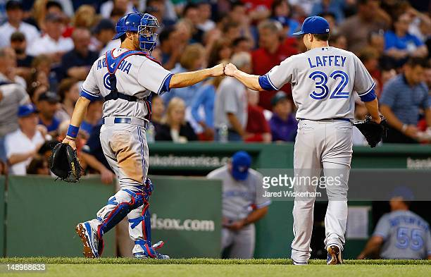 Aaron Laffey of the Toronto Blue Jays is congratulated by teammate JP Arencibia after getting safely out of the third inning against the Boston Red...