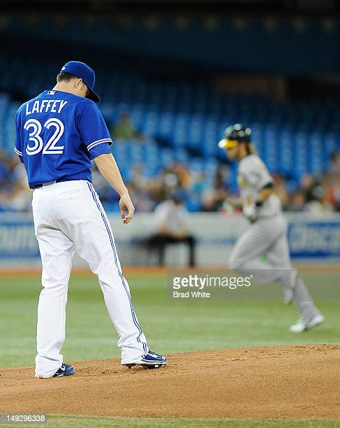 Aaron Laffey of the Toronto Blue Jays looks on as Josh Reddick of the Oakland Athletics runs the bases after hitting a first inning home run during...