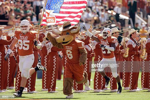 Aaron Lewis of the Texas Longhorns carries the American flag as he leads his team onto the field before the game against the Baylor Bears on November...