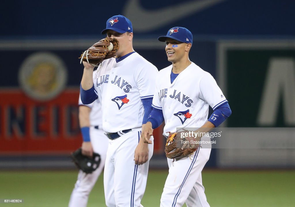 Aaron Loup #62 of the Toronto Blue Jays shares a laugh with Ryan Goins #17 after a double play at second base was reversed following a video replay review in the seventh inning during MLB game action against the Tampa Bay Rays at Rogers Centre on August 14, 2017 in Toronto, Canada.