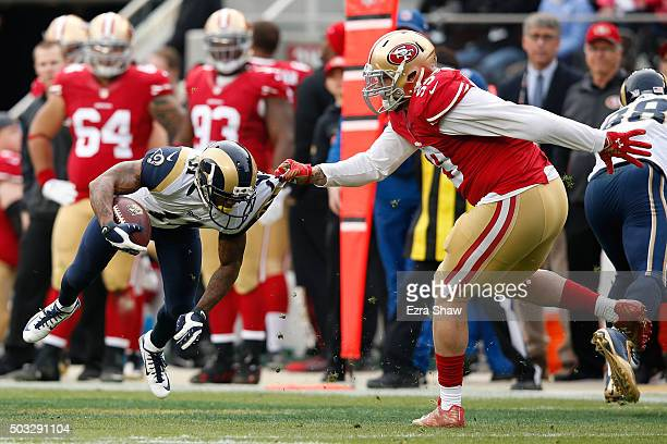 Aaron Lynch of the San Francisco 49ers spins Tavon Austin of the St Louis Rams to the ground during their NFL game at Levi's Stadium on January 3...