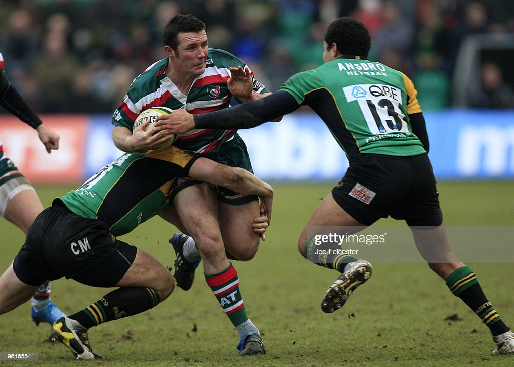 Aaron Mauger of Leicester Tigers is tackled by Chris Mayor and Joe Ansbro (R) of Northampton Saints during the LV Anglo Welsh Cup match between Northampton Saints and Leicester Tigers at the Sixfields Stadium, on February 6, 2010 in Northampton, England.