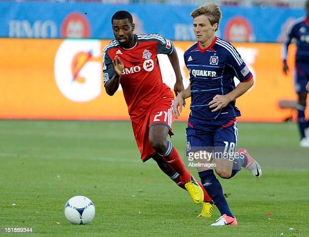 Aaron Maund of Toronto FC carries the ball against Chris Rolfe of the Chicago Fire during MLS action at the BMO Field September 12 2012 in Toronto...
