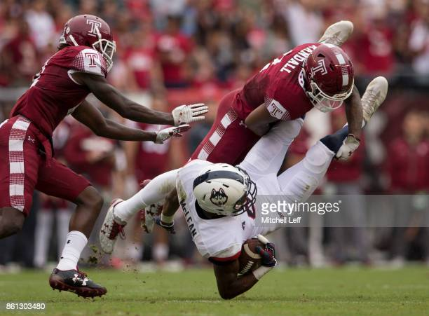 Aaron McLean of the Connecticut Huskies runs with the ball and is tackled by Delvon Randall of the Temple Owls in the second quarter at Lincoln...