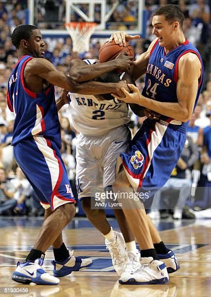 Aaron Miles and Sasha Kaun of the Kansas Jayhawks attempt to grab the ball away from Ravi Moss of the Kentucky Wildcats on January 9 2005 at Rupp...