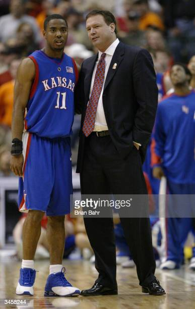 Aaron Miles of the Kansas Jayhawks talks with his head coach Bill Self in the semifinals of the Phillips 66 Big 12 Tournament game against the Texas...
