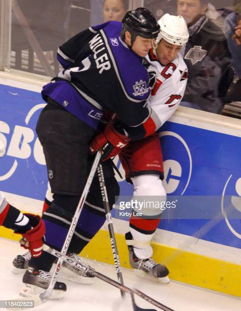 Aaron Miller of the Los Angeles Kings body checks Rod Brind-Amobour of the Carolina Panthers into the boards during 3-2 loss at the Staples Center in...