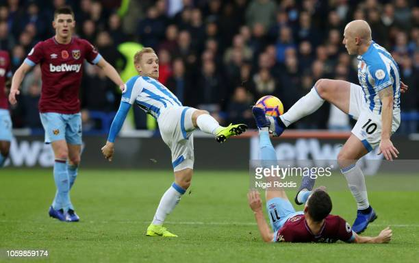 Aaron Mooy and Alex Pritchard of Huddersfield Town battle for possession with Robert Snodgrass of West Ham United during the Premier League match...