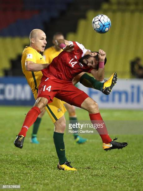 Aaron Mooy of Australia is challenged by Tamer Hag Mohamad of Syria during the 2018 FIFA World Cup Asian Playoff match between Syria and the...