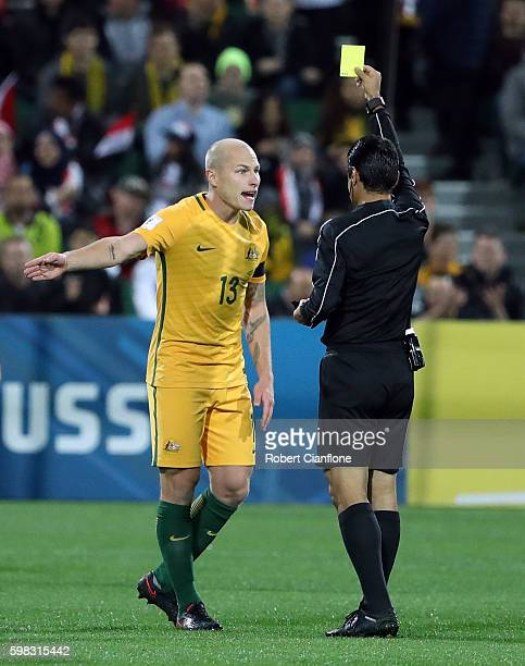 Aaron Mooy of Australia is shown the yellow card by Alireza Faghani during the 2018 FIFA World Cup Qualifier match between the Australian Socceroos...