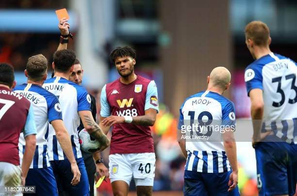 Aaron Mooy of Brighton and Hove Albion is shown a red card by referee David Coote after receiving a second yellow card during the Premier League...