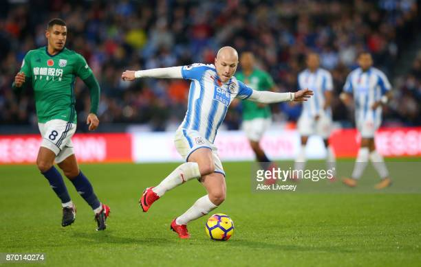 Aaron Mooy of Huddersfield Town and Jake Livermore of West Bromwich Albion in action during the Premier League match between Huddersfield Town and...
