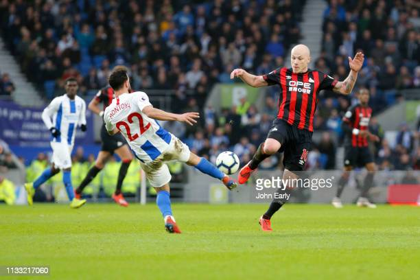 Aaron Mooy of Huddersfield Town and Martin Montoya of Brighton Hove Albion during the Premier League match between Brighton Hove Albion and...