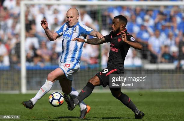 Aaron Mooy of Huddersfield Town battles for possession with Alexandre Lacazette of Arsenal during the Premier League match between Huddersfield Town...