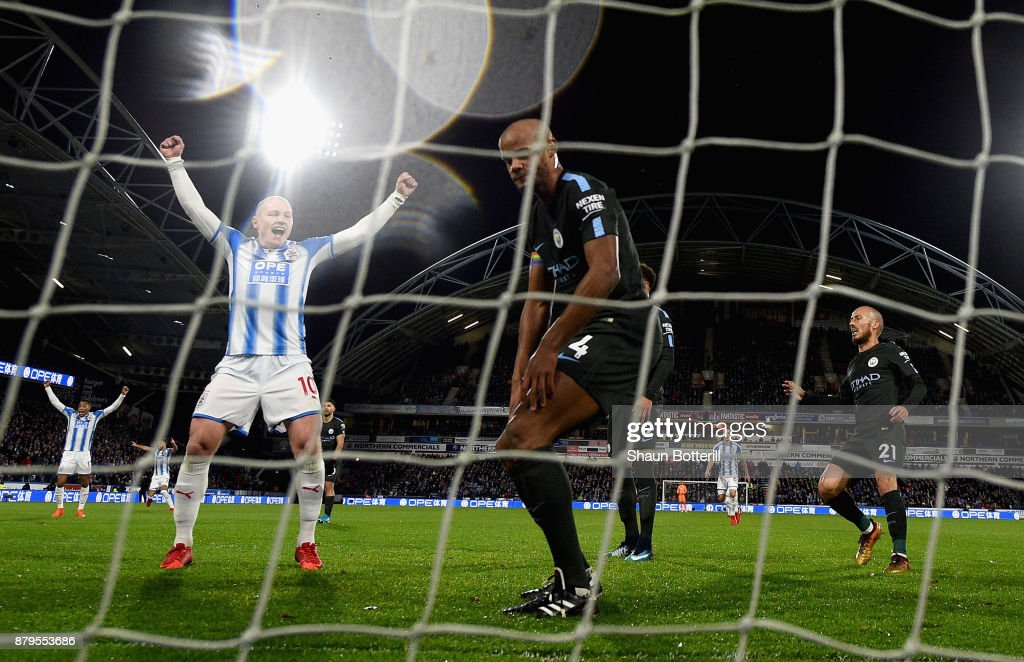 Aaron Mooy of Huddersfield Town celebrates after Nicolas Otamendi of Manchester City scored the first own goal as Vincent Kompany of Manchester City looks dejected during the Premier League match between Huddersfield Town and Manchester City at John Smith's Stadium on November 26, 2017 in Huddersfield, England.