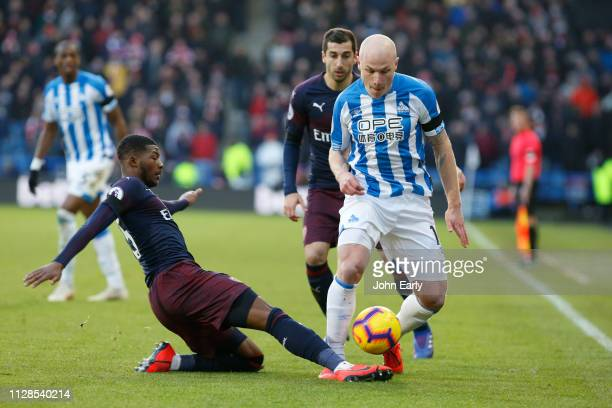 Aaron Mooy of Huddersfield Town is tackled by Ainsley MaitlandNiles of Arsenal during the Premier League match between Huddersfield Town and Arsenal...