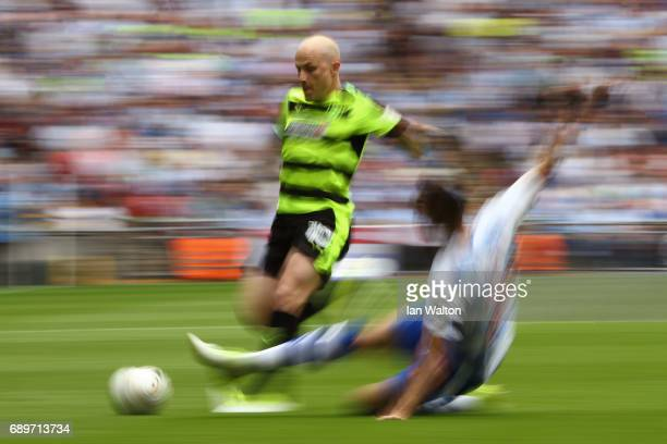Aaron Mooy of Huddersfield Town is tackled by Joey van den Berg of Reading during the Sky Bet Championship play off final between Huddersfield and...