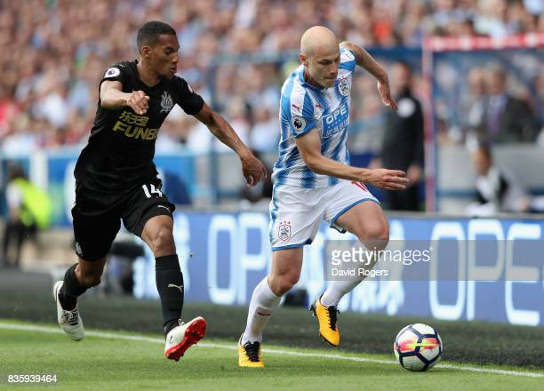 Aaron Mooy of Huddersfield Town moves away from Isaac Hayden during the Premier League match between Huddersfield Town and Newcastle United at John...