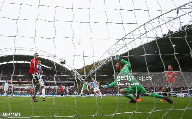 Aaron Mooy of Huddersfield Town scores their first goal past goalkeeper David De Gea of Manchester United during the Premier League match between...