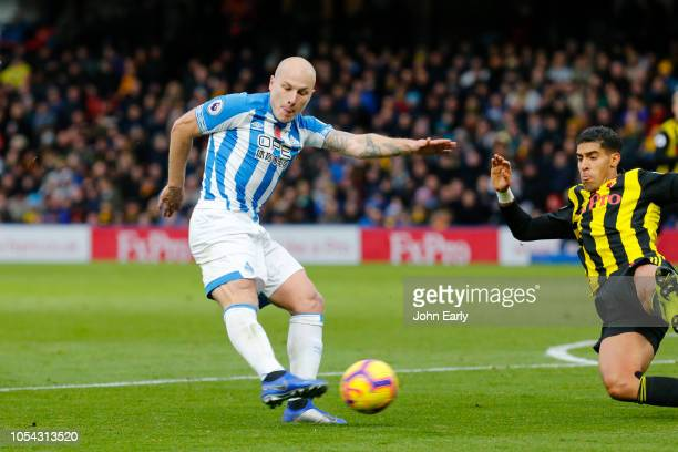 Aaron Mooy of Huddersfield Town shoots under pressure from Adam Masina of Watford FC during the Premier League match between Watford FC and...