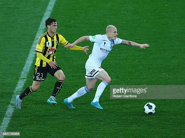 Aaron Mooy of Melbourne City is chased by Matthew Ridenton of the Phoenix during the FFA Cup Round of 16 match between Melbourne City FC and...