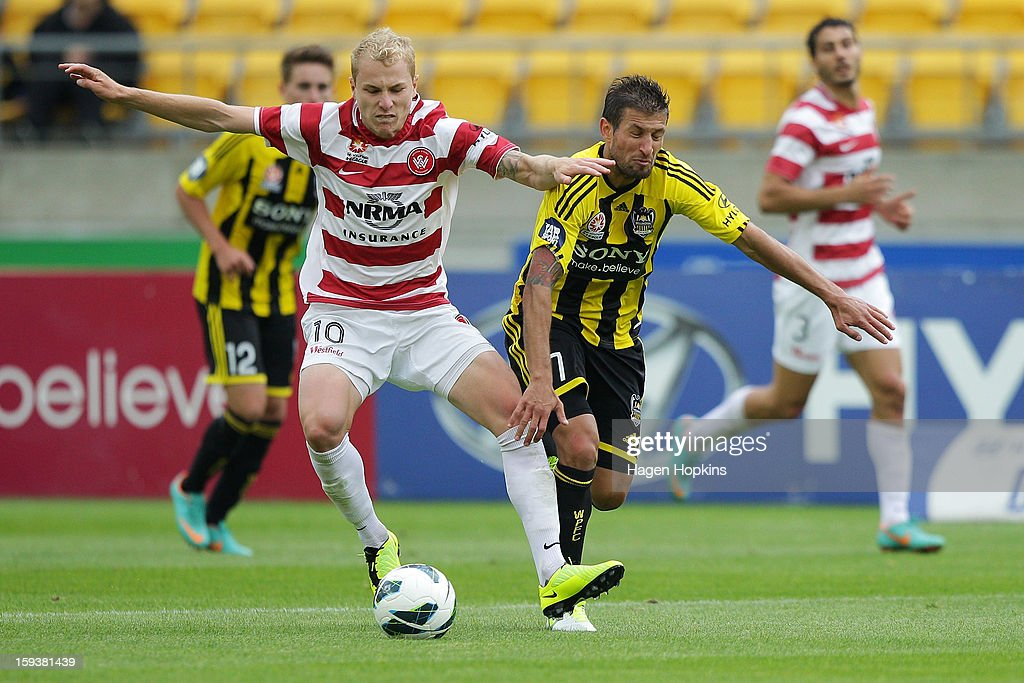 Aaron Mooy of the Wanderers holds off the defence of Vince Lia of the Phoenix during the round 16 A-League match between the Wellington Phoenix and the Western Sydney Wanderers at Westpac Stadium on January 13, 2013 in Wellington, New Zealand.