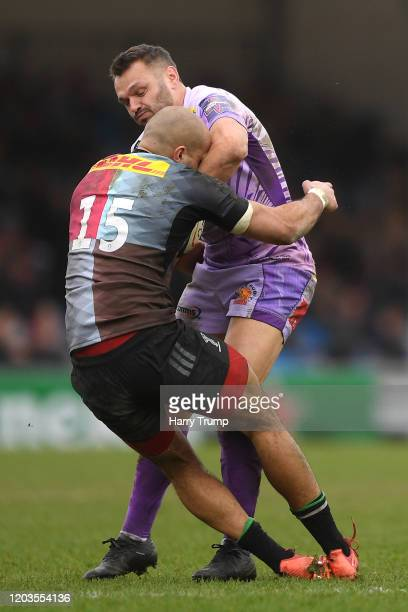 Aaron Morris of Harlequins is knocked over as he attempts to tackle Phil Dollman of Exeter Chiefs during the semi-final of the Premiership Rugby Cup...