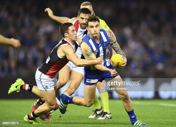 Aaron Mullett of the Kangaroos handballs whilst being tackled by Jade Gresham of the Saints during the round 13 AFL match between the North Melbourne...