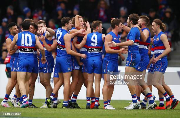 Aaron Naughton of the Bulldogs is congratulated by his teammates after kicking a goal during the round eight AFL match between the Western Bulldogs...