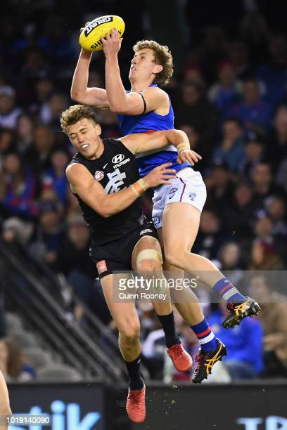 Aaron Naughton of the Bulldogs marks over the top of Patrick Cripps of the Blues during the round 22 AFL match between the Carlton Blues and the...