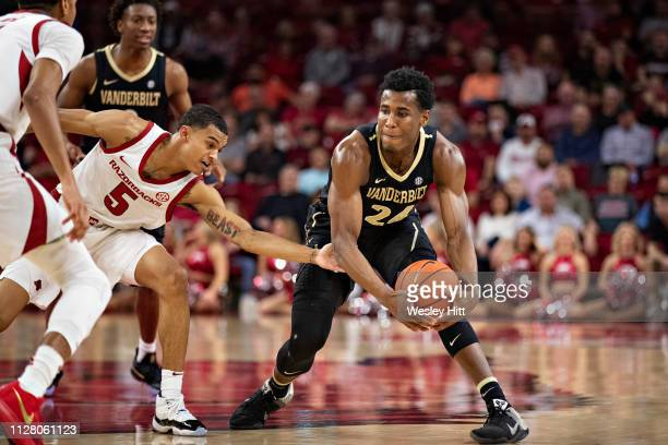 Aaron Nesmith of the Vanderbilt Commodores looks to make a pass while being guarded by Jalen Harris of the Arkansas Razorbacks at Bud Walton Arena on...
