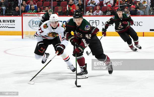 Aaron Ness of the Arizona Coyotes skates with the puck ahead of Kirby Dach of the Chicago Blackhawks during the third period of the NHL hockey game...