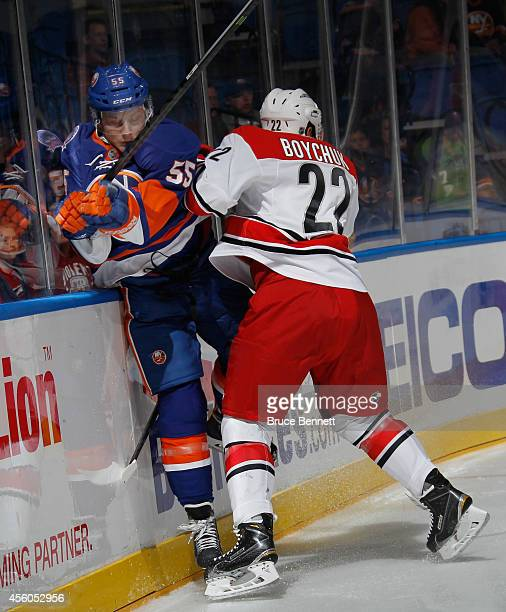 Aaron Ness of the New York Islanders is hit into the boards by Zach Boychuk of the Carolina Hurricanes during the first period at the Nassau Veterans...