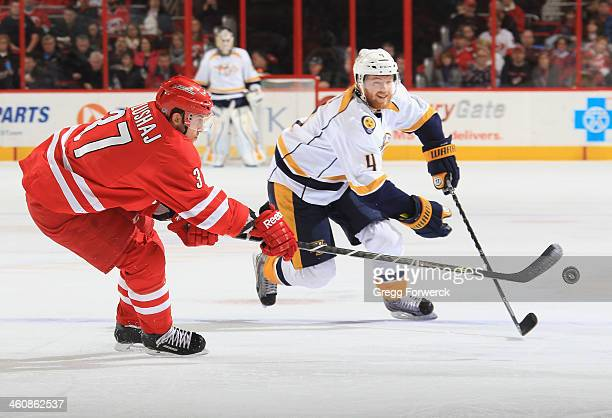 Aaron Palushaj of the Carolina Hurricanes battles for the puck against Ryan Ellis of the Nashville Predators during their NHL game at PNC Arena on...