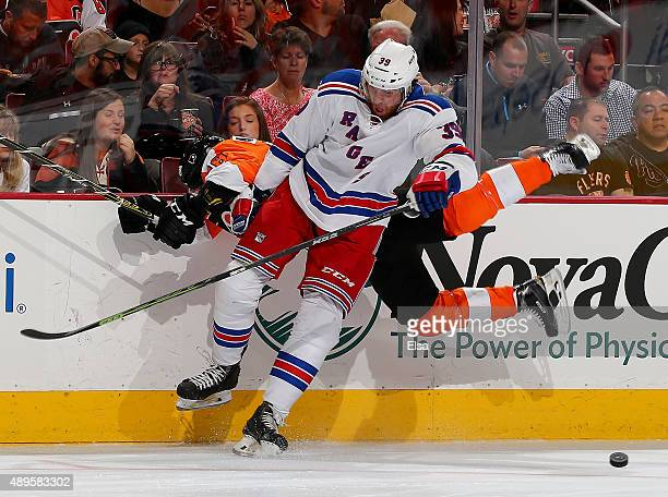 Aaron Palushaj of the Philadelphia Flyers is checked by Brett Bellemore of the New York Rangers in the first period on April 7, 2015 at the Wells...