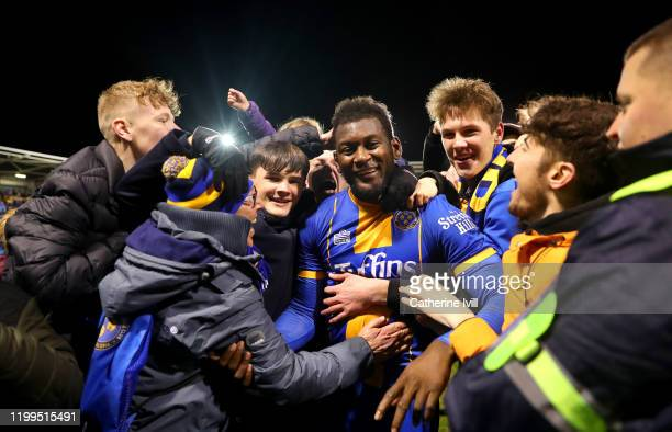 Aaron Pierre of Shrewsbury Toshoots is mobbed by fans as he celebrates victory after the FA Cup Third Round Replay match between Shrewsbury Town and...