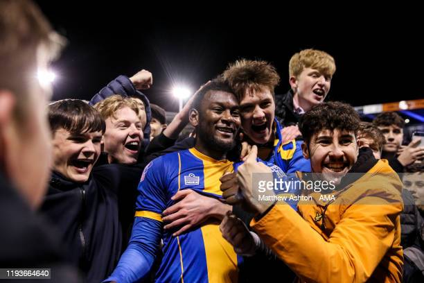 Aaron Pierre of Shrewsbury Town is mobbed by fans at full time who celebrate during the FA Cup Third Round Replay match between Shrewsbury Town and...